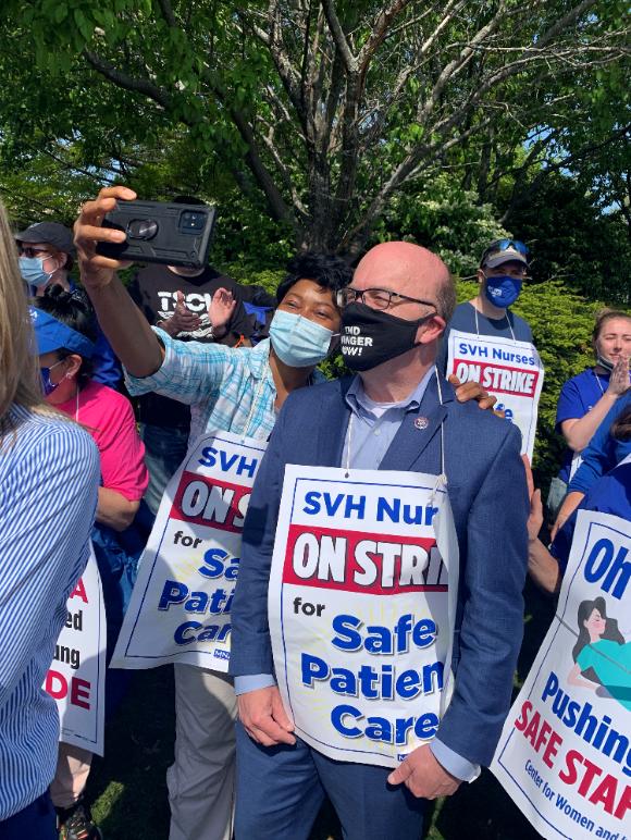 A striking nurse taking a selfie with Representative Jim McGovern
